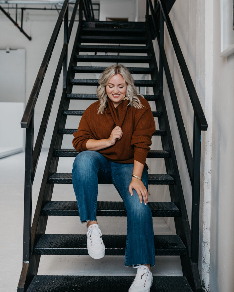 Woman sitting on stairs wearing Burgundy Sweater and Denim Jeans.  SellEatLove.com