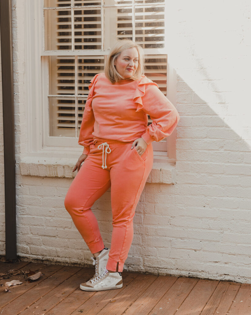 Spring Target Finds - Woman standing in front of white brick house wearing a pinkish peach ruffle sleeve sweater and matching jogger pants with sneakers