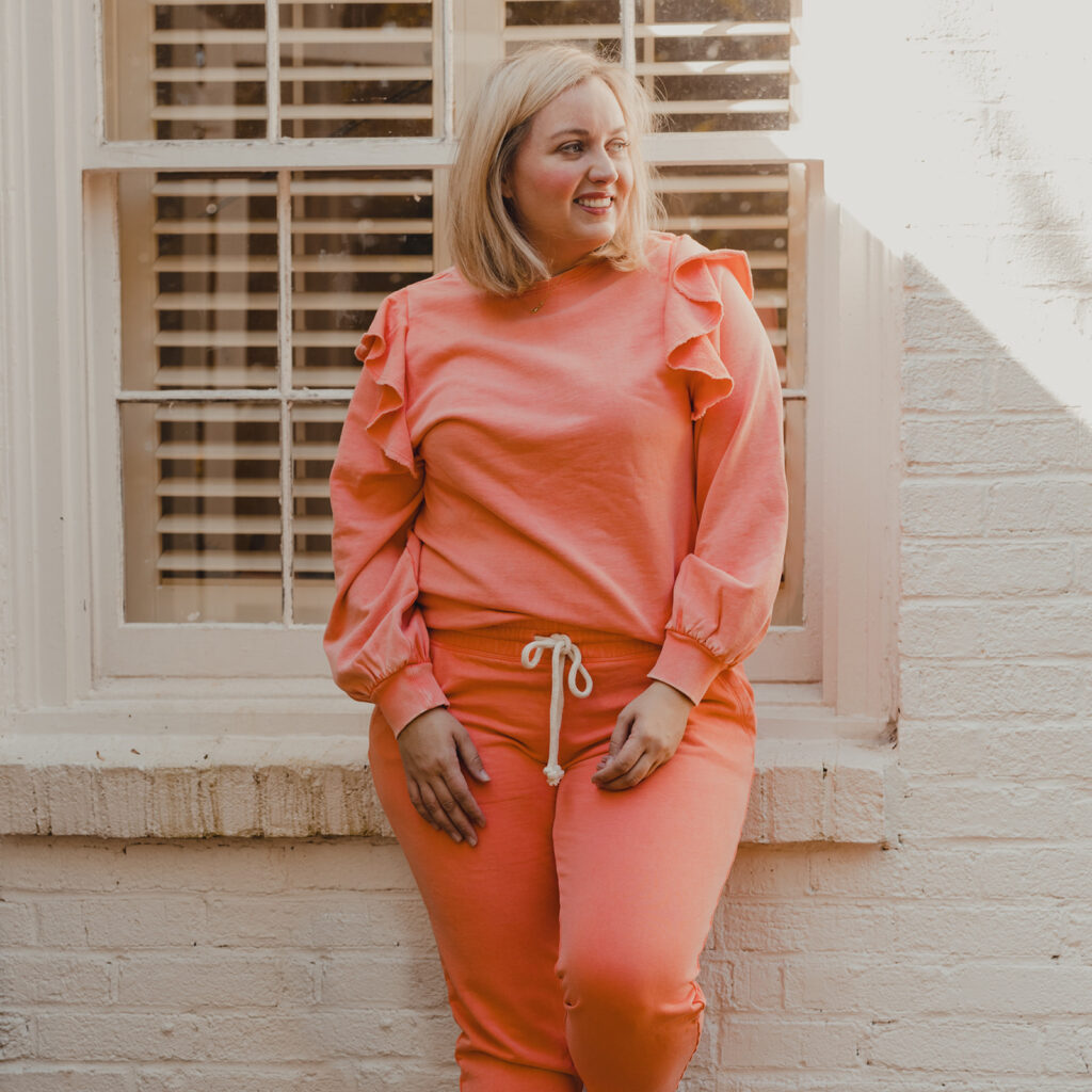 Spring Target Finds - Woman standing in front of white brick house wearing a pinkish peach ruffle sleeve sweater and matching jogger pants
