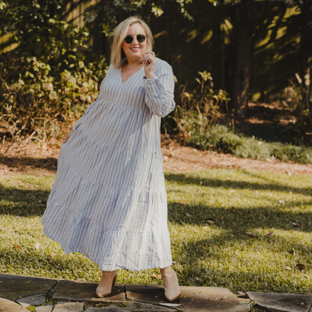 Spring Target Finds - Woman swirling in front of a tree wearing a white and blue striped tiered dress and sunglasses and tan booties