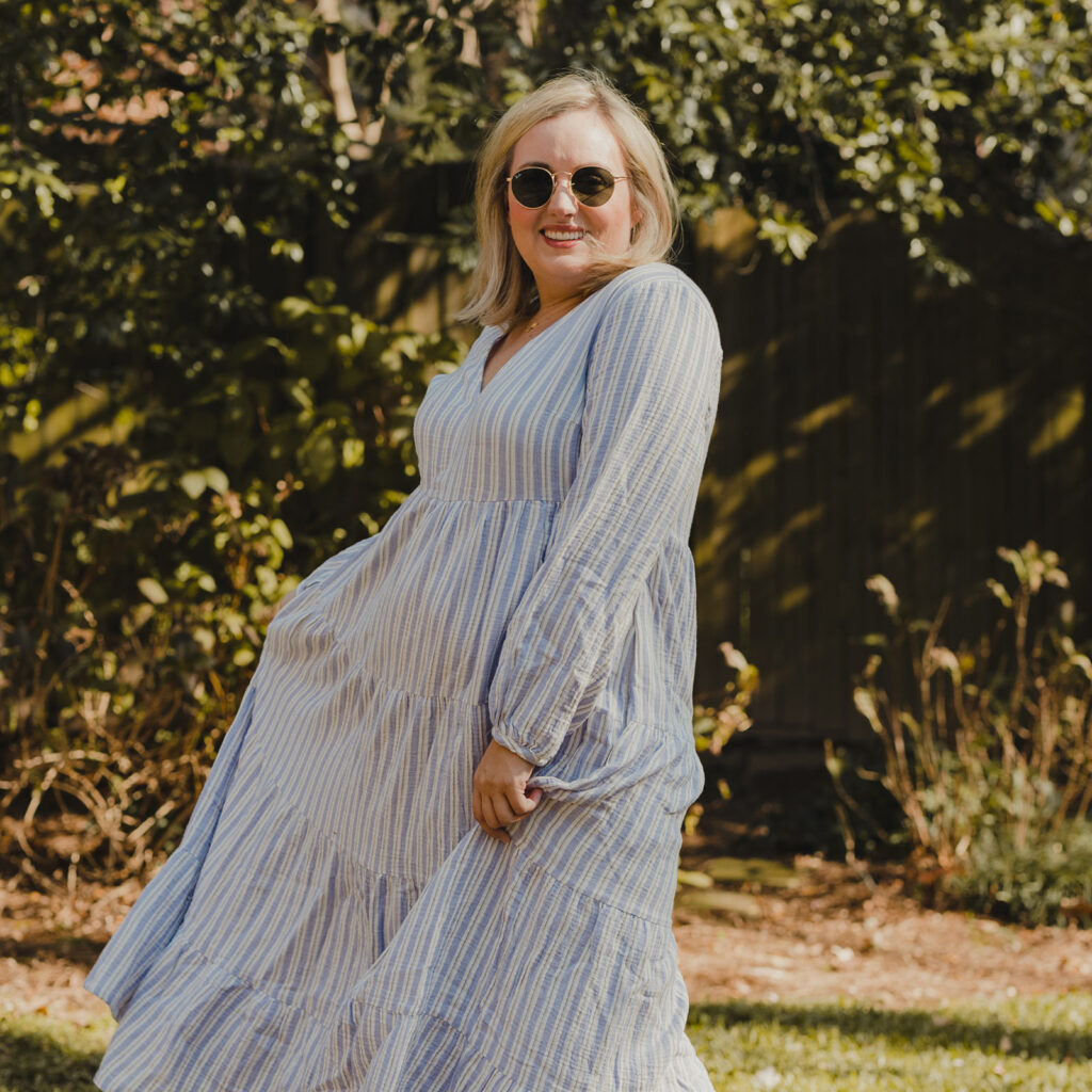 Spring Target Finds - Woman swirling in front of a tree wearing a white and blue striped tiered dress and sunglasses