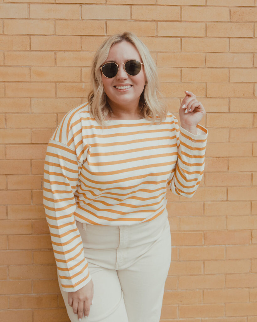 image of woman wearing wide leg pants with striped shirt in front of brick wall