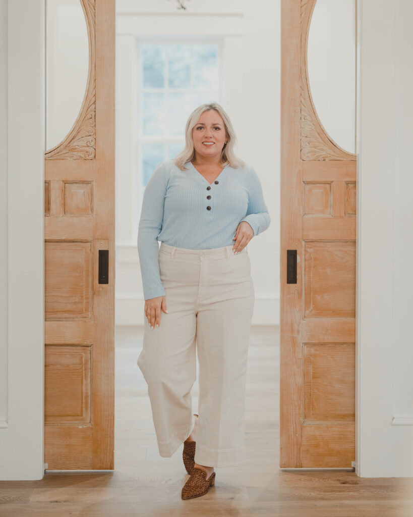 4 Ways To Style Wide Leg Pants woman standing in between pocket doors wearing cream wide leg pants and light blue pastel button up shirt with woven mules