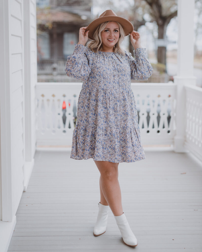 Spring Dresses from Target - woman standing outside wearing a short-tiered floral long sleeve dress with brown hat and white booties