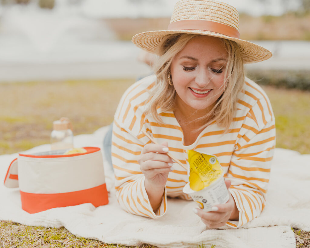 Two Good Yogurt - woman outside in hat having a picnic with Two Good Good Save Lemon flavored Greek Yogurt
