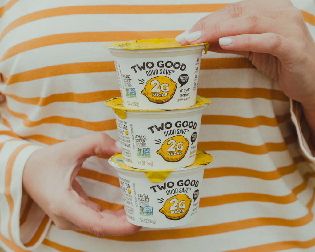 Two Good Yogurt -picture holding Two Good Good Save Lemon flavored Greek Yogurt