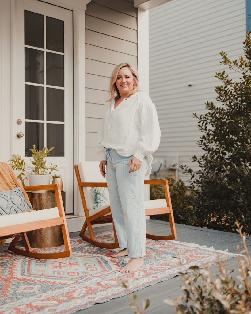 4 Ways To Style Wide Leg Pants woman standing on porch wearing denim wide leg jeans with white gauze top