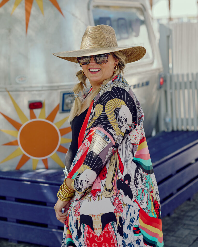 5 Ways to Style a Kimono - Woman wearing Black Bodysuit and Denim Shorts with a Kimono, hat and gold jewerly.