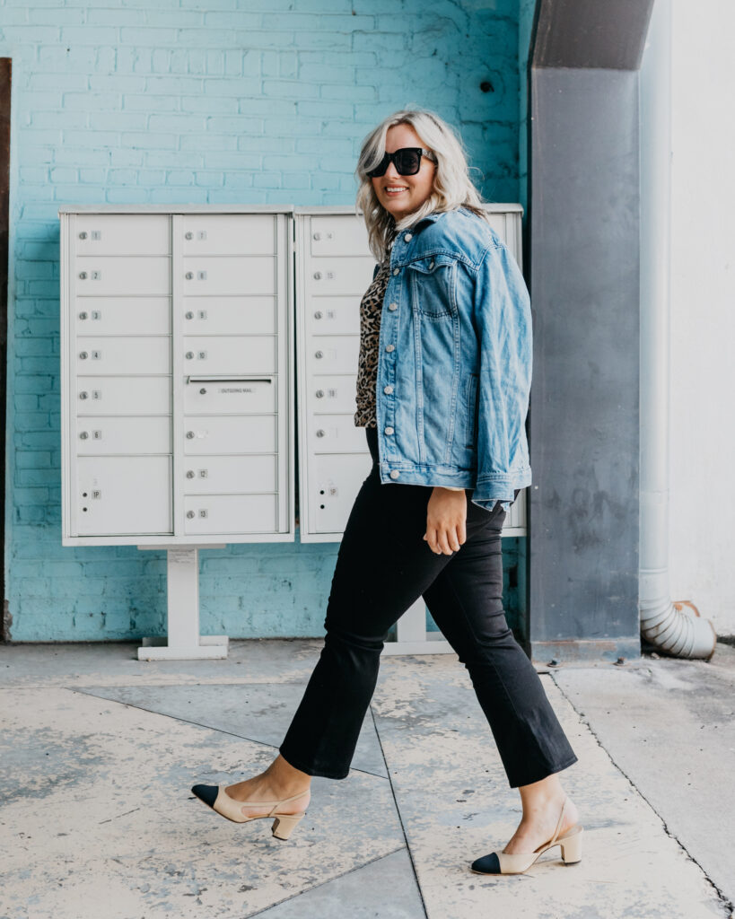 Woman wearing Denim Jacket, Black Denim Jeans and animal print top.